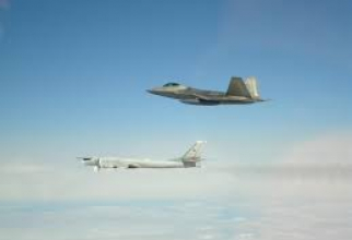 Un bombardier strategic rus Tupolev Tu-95 este văzut fiind însoțit de un avion de luptă american F-22 în spațiul aerian internațional în largul coastei Alaska, 21 mai 2019.
