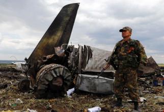 Un separatist pro-rus stă de pază la locul prăbușirii avionului de transport al armatei ucrainene Il-76, Luhansk 14 iunie 2014