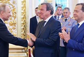 De la stânga la dreapta: Vladimir Putin, Gerhard Schroeder, Dmitri Medvedev. În spate, în uniformă militară, ministrul rus al apărării Serghei Şoigu.
