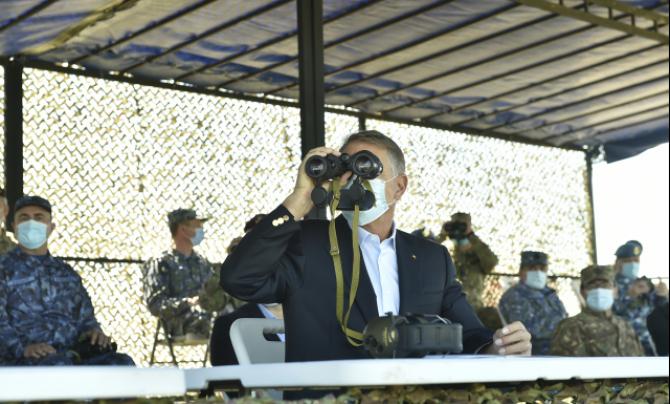 Președintele Klaus Iohannis, urmărind exercițiile Armatei României, în poligonul Smârdan. Sursă foto: Administrația Prezidențială