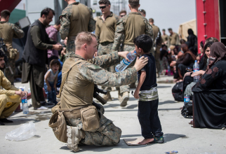 Un soldat american, oferind asistență unui copil în timpul haosului de pe aeroportul din Kabul. Sursă foto: U.S. Department of Defense (DoD)