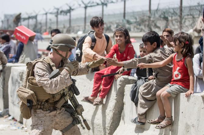 Un soldat american, jucându-se cu câțiva copii afgani în timpul misiunilor de evacuare de pe aeroportul din Kabul. Sursă foto: U.S. Department of Defense (DoD)