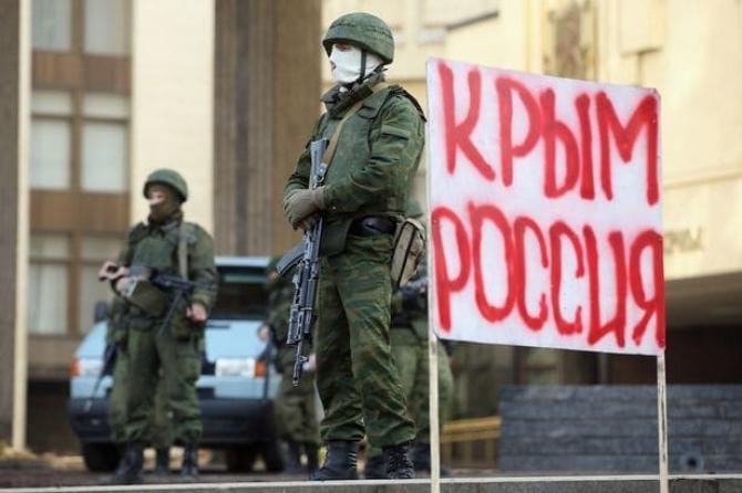 """Celebri """"omuleți verzi"""" ruși, apărând în 2014 sediul Parlamentului din Crimeea, alături de un semn pe care scrie """"Crimeea Rusia"""", sursă foto: NATO"""